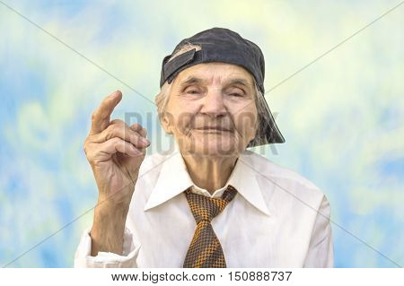 Elderly woman with cap showing middle finger. Selective focus.