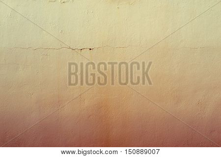 the abstract textured background of an old surface of the plastered wall of a motley yellow color tonality