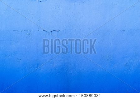 the abstract textured background of an old surface of the plastered wall of a motley blue color tonality