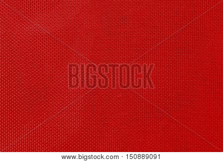 woven texture synthetic fabric with an interlacing of threads of red color for a background or for wallpaper