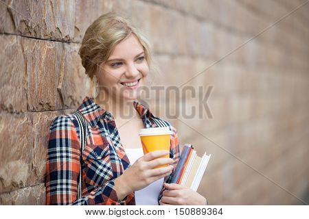 Portrait of a smiling student girl with books and coffee against the brick wall. Back to school concept photo