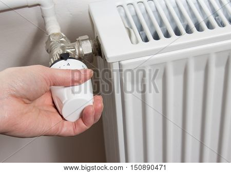 Closeup of a radiator thermostat with woman hand