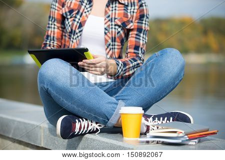 Student sitting turkish at bridge with tablet, copybook, coffee near, waterline behind. Back to school concept photo, closeup