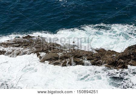 Wave splashing over a rock on Caleta Negra beach in Ajuy on Fuerteventura. Canary Island Spain