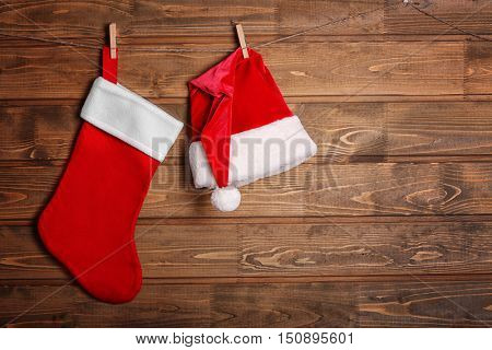 Christmas stocking and Santa Claus hat hanging against wooden background