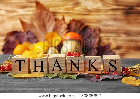 Autumn composition of leaves, berries and cubes with word THANKS on wooden surface against blurred background. Thanksgiving day concept