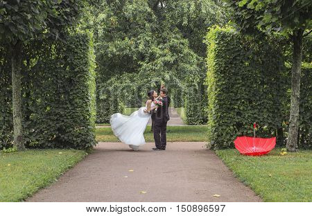 very beautiful bride with groom hugging and dancing in green park, real wedding couple together forever happy smiling, lifestyle real people concept close up