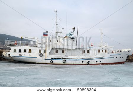 Lake Baikal, Russia - March 21, 2016: Ship and fisher boats on the dock in Large Goloustnoye Village. Russia Baikal Lake.
