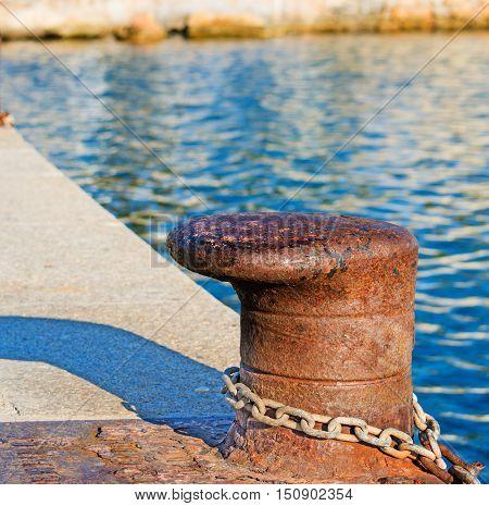 close up of a rusty bollard on the dock