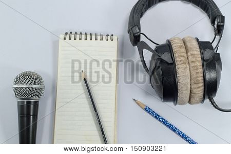 blank notebook in top view with music concept whitebackground headphones