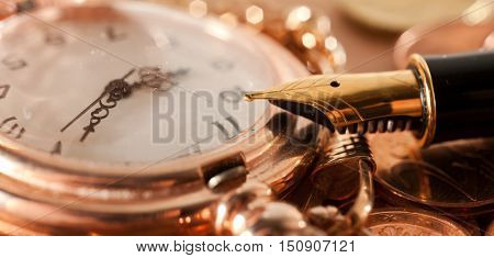 Gold fountain pen and pocket watch close-up