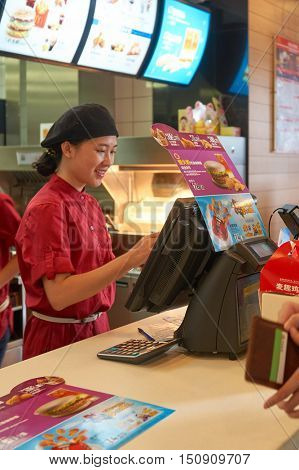 SHENZHEN, CHINA - OCTOBER 22, 2015: indoor portrait of a worker at McDonald's restaurant in Shenzhen. McDonald's is the world's largest chain of hamburger fast food restaurants.