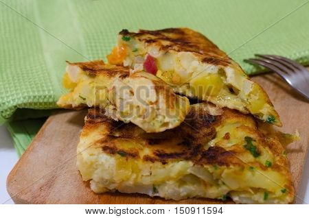Typical homemade Spanish tortilla omelette with potatoes and jamon