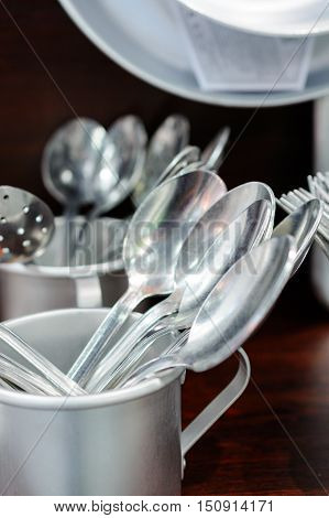 Aluminum tablespoons are in an aluminum cup. Soviet aluminum dishes.
