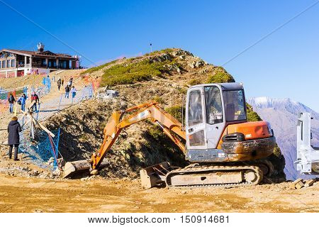 SOCHI RUSSIA - OCTOBER 31 2015: Small excavator Hitachi conducts excavation in mountains. Hills and peaks of Caucasus mountains. Krasnaya Polyana - Alpine ski resort constructed from 2003 to 2011 for Sochi games. Rosa Khutor Sochi Russia