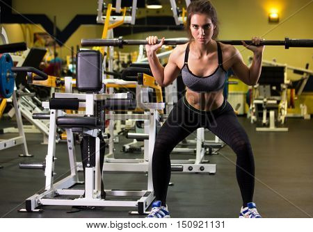 Fitness. Sporty woman exercising with barbell in gym.