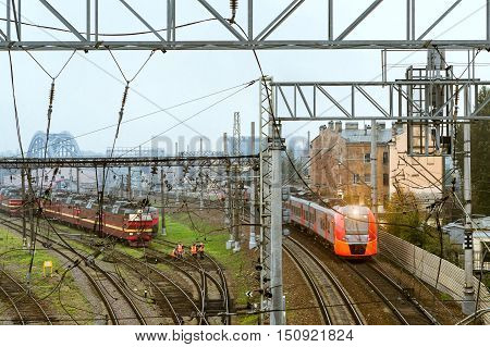 SAINT-PETERSBURG RUSSIA - September 27 2016: modern locomotive pulling a high-speed electric train Lastochka on rails. Technical railway station - operational locomotive depot. Workers in overalls serve rail journey. Transport infrastructure of Russian Ra
