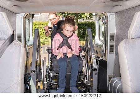 Working together with disability, a disabled child in a wheelchair being cared for by voluntary care worker