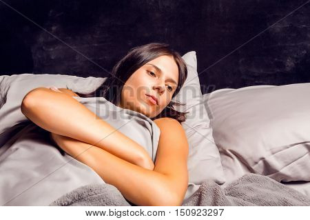 Woman lying in bed on a dark background with open eyes. Beautiful young brunette in bad mood lying in bed.