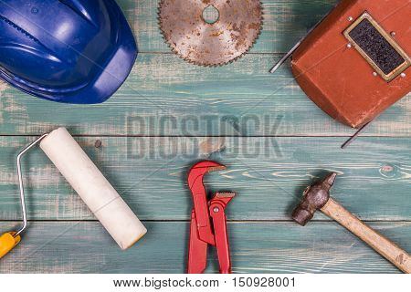 Construction concept. Roller hammer hard hat red adjustable pipe wrench circulat saw blade and weldign mask on nice green wood background.