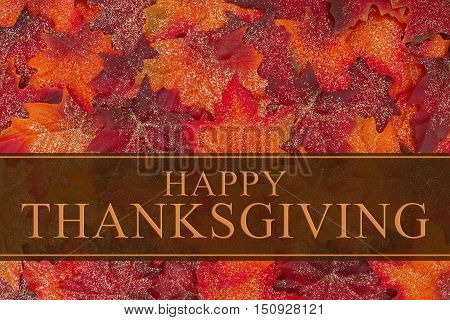 Happy Thanksgiving Greeting Some glittery fall leaves and a greeting card with text Happy Thanksgiving