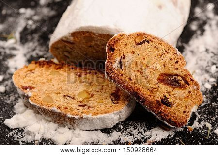 Stollen christmas cake with sugar icing on stone plate closeup