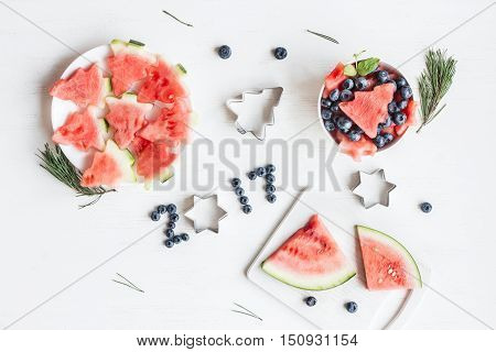 Christmas fruit salad of watermelon and blueberries for kids. Slices of watermelon in the shape of christmas trees. Top view flat lay