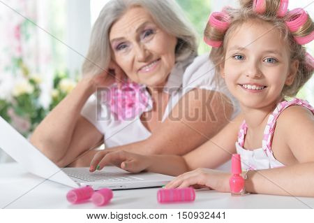 Cute little girl in  hair curlers  with granny using laptop at home