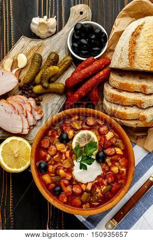 Solyanka - Russian traditional meat soup on wooden background
