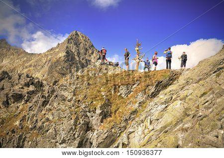 HIGH TATRA MOUNTAINS - SEPTEMBER 15 2016: Tourists on mountain pass admiring views in High Tatra Slovakia.