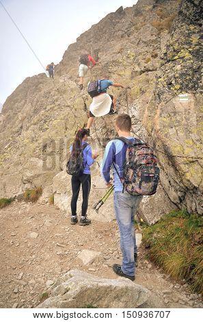 HIGH TATRA MOUNTAINS SLOVAKIA - SEPTEMBER 15 2016: Tourists on a mountain trail in High Tatra Slovakia.
