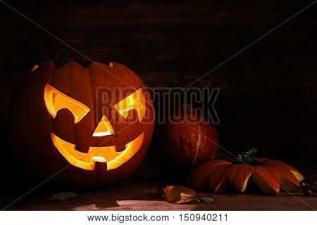 Carved halloween pumpkin with a scary glowing face on dark rustic wood as an autumn decoration copy space