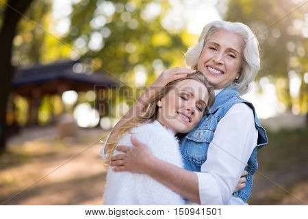 I will try to help you. Gray haired beautiful kind woman hagging her daughter and smiling while standing in the park.