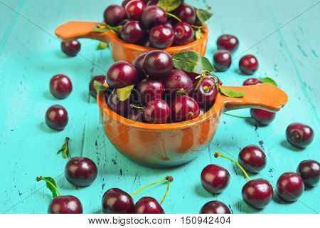 Red ripe cherries in two brown bowl ceramic red cherries on wooden table green cherry leaves green wooden background