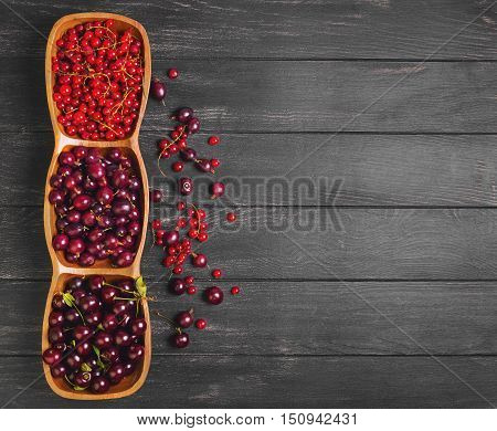 Garden fresh red berry fruit. Gooseberry cherry red currant. Red berries are scattered on dark wooden background black gooseberry cherry red currant. Top view.