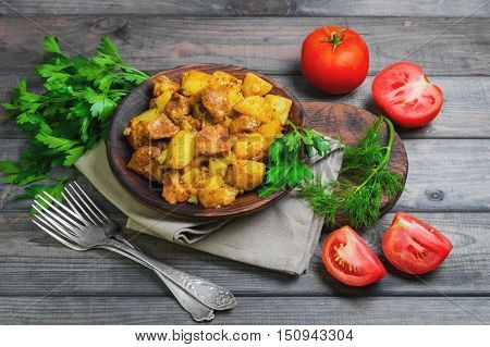 Stewed potatoes with meat Goulash additional ingredients for stewed with potatoes tomatoes dill parsley gray wooden background