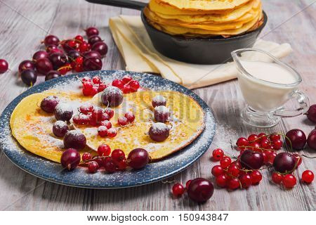 Pancakes fritters in cast iron skillet stack hash browns pancakes on plate with berries. Berries for pancakes crepes red currants gooseberries cherries sour cream. Light white wooden background.