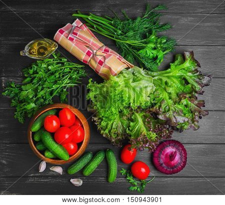 Vegetable Ingredients for cooking vegetable salad. Vegetables cucumber cherry tomatoes purple onion garlic cloves parsley dill lettuce salad leaves vegetable oil. Black wood background Top view