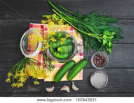 Canning pickling fresh homemade cucumbers pickling or salting. Greens for canning pickling cucumbers dill parsley garlic pepper salt. Fresh cucumbers on cloth. Dark black wooden background. Top view.