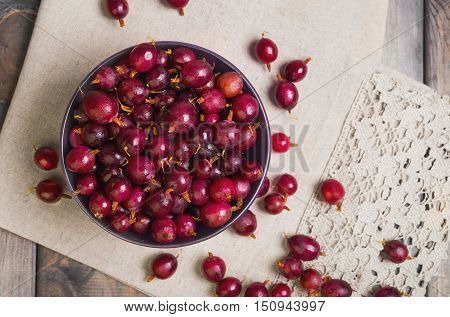 Ripe red purple berry gooseberries in purple bowl on gray wooden table. Gooseberry berries on the table cloth. Top view.