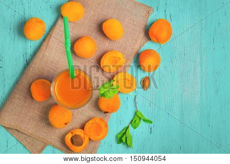 Glass with fresh apricot juice drink the whole fruit of apricot mint apricot halves and pits green wood background top view empty place for text