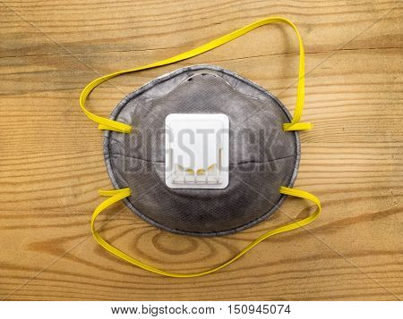 Industrial respirator with valve protects against dust on wooden background