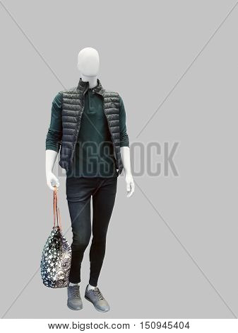 Full length male mannequin dressed in sleeveless jacket green shirt and black jeans over gray background. No brand names or copyright objects.