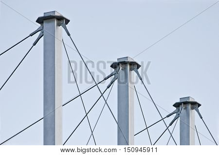 Tied Suspension Roof Cables Three Tall Grey Masts Cable-suspended Swooping Rooftop Pylon Anchors Pale Blue Summer Sky Large Detailed Horizontal Closeup Contemporary Construction Concept