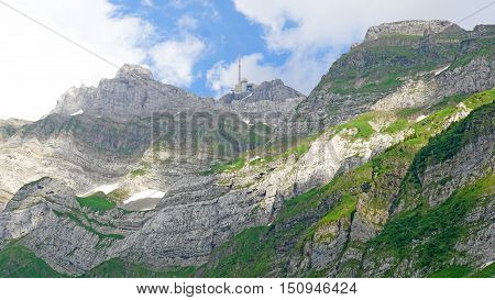 steep rock faces of the Alpstein in the Appenzell Alps in Switzerland, on the mountaintop Saentis is a radio tower, blue sky with white clouds