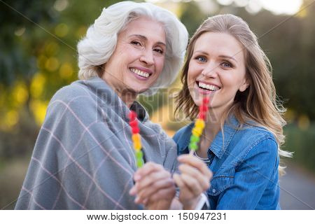 We love sweats. Pretty glad mother and daughter smiling and showing lollypops while having a walk.