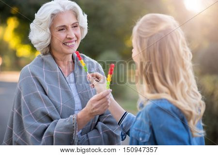 Sweet life. Cheerful beautiful mother and daughter smiling and having a walk while showing each other lollypops.