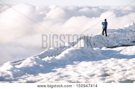 Clouds, mountains, snow and man (winter landscape)