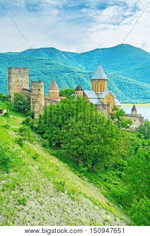 The old stone towers and Assumption Church's dome of Ananuri Castle among the greenery on the steep at Aragvi River Mtskheta-Mtianeti Georgia.