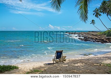 Simple chair on sandy beach by Indian Ocean on a beach in Sri Lanka Asia.
